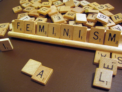 "Photo of scrabble tiles forming the word ""FEMINISM"""